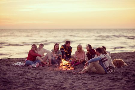 Photo pour Group of young friends sitting by the fire at autumn beach, grilling sausages and drinking beer, talking and having fun filter - image libre de droit