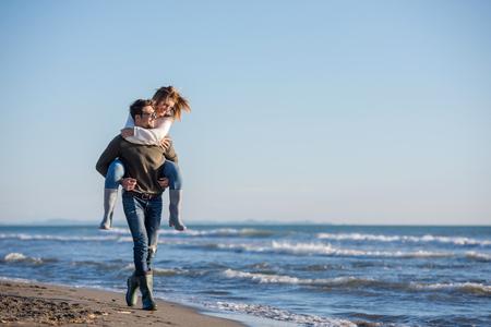 Photo pour Men Giving Piggy Back Rides to his girlfriend At Sunset By The Sea, autumn time - image libre de droit