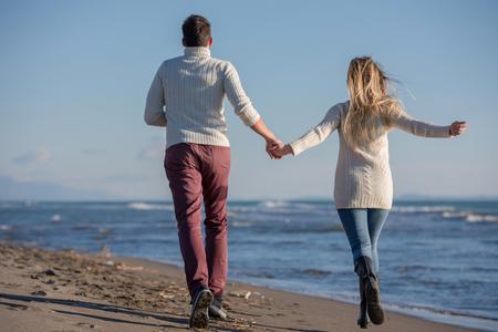 Foto de Young couple having fun walking and hugging on beach during autumn sunny day - Imagen libre de derechos