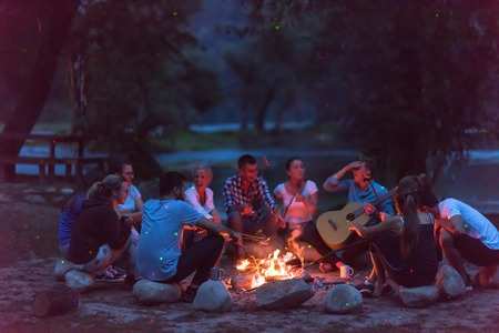 Foto de a group of happy young friends relaxing and enjoying  summer evening around campfire on the river bank - Imagen libre de derechos