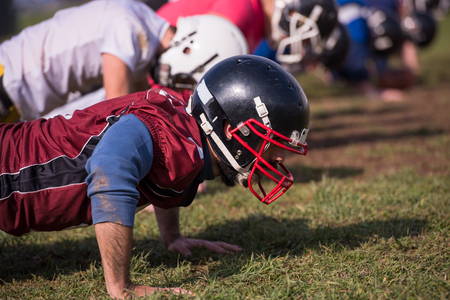 Photo pour american football team doing push ups during training at the field - image libre de droit