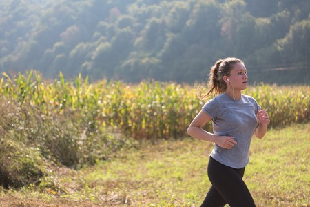 Photo pour A young woman enjoying in a healthy lifestyle while jogging along a country road, exercise and fitness concept - image libre de droit