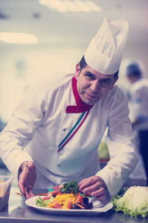 Photo for chef serving vegetable salad on plate in restaurant kitchen - Royalty Free Image