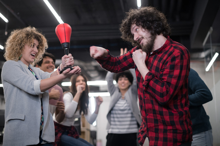 Foto de multiethnics startup business team of software developers having fun while boxing at office,excited diverse employees laughing enjoying funny activity at work break, creative friendly workers playing game together - Imagen libre de derechos