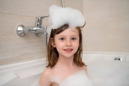 Photo pour Little girl playing with soap foam in bath - image libre de droit