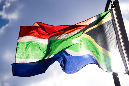 Foto de Waving flag from South-Africa with sun shining behind it against sky - Imagen libre de derechos