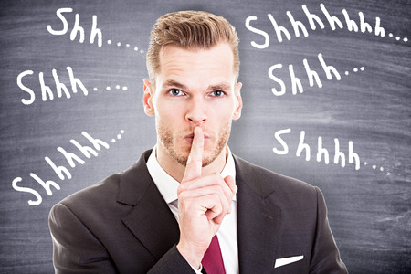 Photo pour Businessman with finger on lips asking for silence - image libre de droit