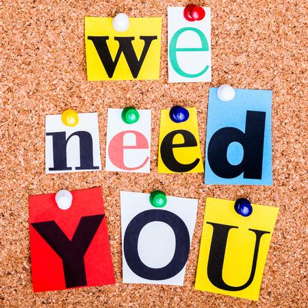 Foto de The phrase we need you in cut out magazine letters pinned to a cork notice board - Imagen libre de derechos