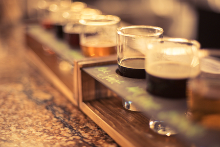 Foto de closeup of a beer flight on a granite bar top at local micro brewery - Imagen libre de derechos