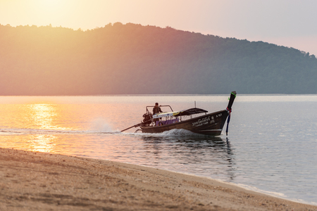 Foto de Nopparat Thara, Krabi Province, Thailand - January 14, 2019:  One men on thai long-tail motor boat floats in sea water in the evening from touristic day tour to the local islands - Imagen libre de derechos