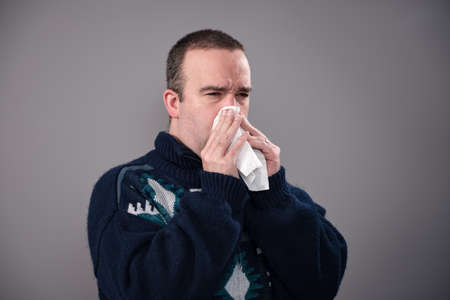 Photo for A sick man in his 30's is blowing his nose, shot against a grey background - Royalty Free Image
