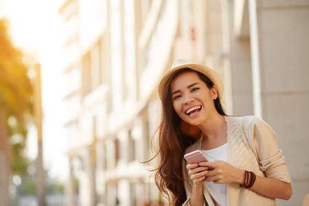 Foto de Happy young Asian woman with smartphone standing in the street - Imagen libre de derechos