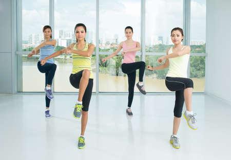 Foto de A group of young girls doing aerobics steps in the sport class - Imagen libre de derechos