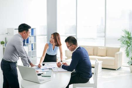 Foto de Asian business partners working with papers in the office - Imagen libre de derechos