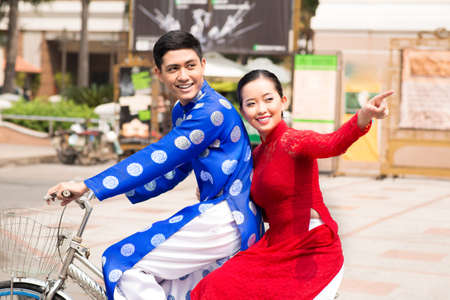 Two Vietnamese riding bicycle in traditional clothes