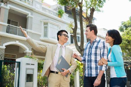 Photo pour Estate agent showing a house to the young family - image libre de droit
