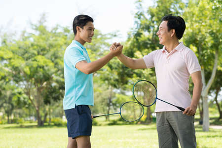 Copy-spaced image of a son and dad having friendly badminton competition and handshaking in the sign of friendship