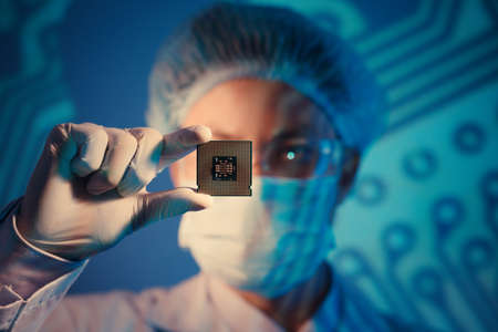 Photo pour Computer engineer holding microchip for detailed analysis on the foreground - image libre de droit