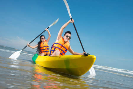 Photo for Cheerful couple paddling in kayak - Royalty Free Image