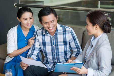 Photo pour Vietnamese couple and saleswoman discussing contract - image libre de droit