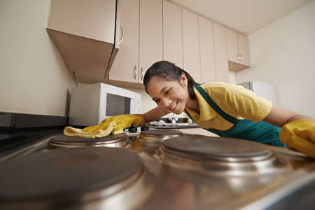 Photo pour Woman in rubber gloves cleaning electric stove - image libre de droit