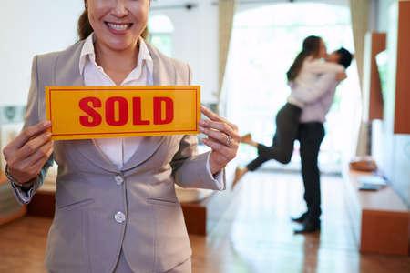 Photo pour Happy real estate agent holding sold sign - image libre de droit