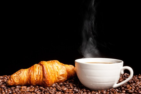 Photo for Croissant and steaming coffee beans in close up photo. Delicious morning drink and snack - Royalty Free Image