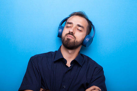 Photo pour Young man listening to music through headphones on blue background - image libre de droit
