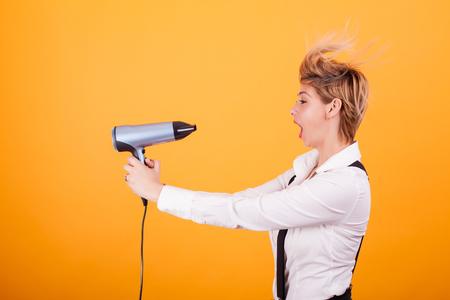 Foto de Beautiful young woman with blonde short hair using hairdryer over yellow background.. Hair care. Funny coiffure. - Imagen libre de derechos