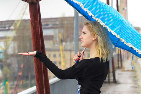 Girl with umbrella walking under the rain cathing the raindrops