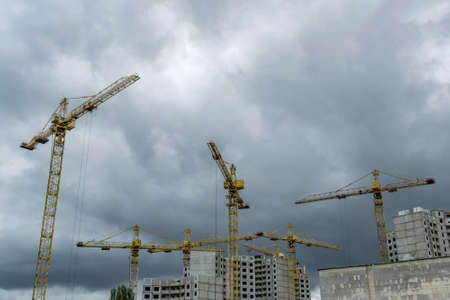 Photo pour Construction cranes developing residential buildings under the stormy sky - image libre de droit