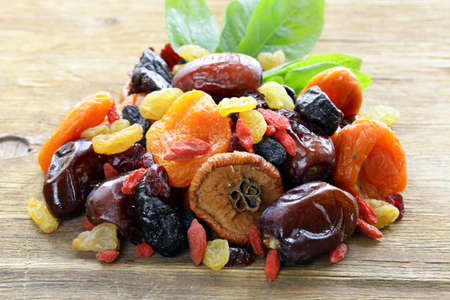 Photo for Assorted dried fruits raisins apricots figs prunes goji cranberries on a wooden background - Royalty Free Image