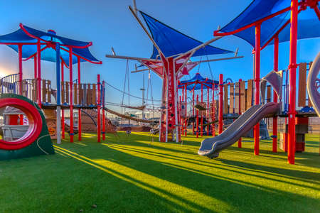 Photo for Sun light cast on playground red and blue colors - Royalty Free Image
