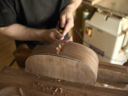 Photo for Luthier makes a neck block on a classical guitar. - Royalty Free Image