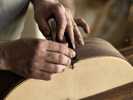 Photo for Luthier Install Binding on an guitar. Chamfering on the body of the guitar. - Royalty Free Image