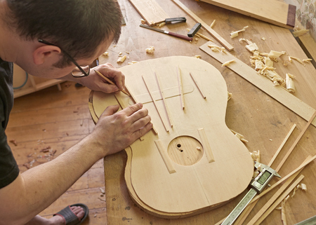 Photo for Marking and Pasting brace to the soundboard of a classical guitar. Production of classical guitar. - Royalty Free Image
