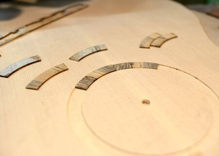 Photo for The guitar master pastes the rosette into a classical guitar. - Royalty Free Image