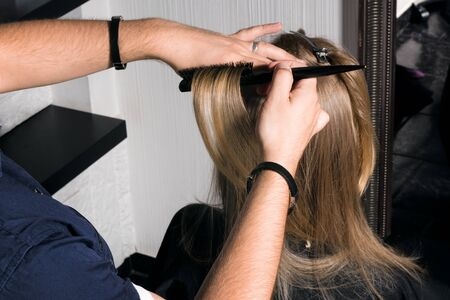 Foto de Young woman doing hair styling in the salon. The hairdresser increases the volume at the roots of the hair. - Imagen libre de derechos