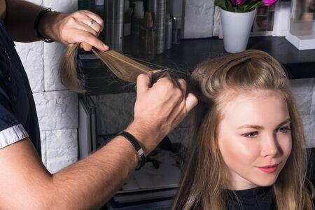 Foto de Young woman doing hair styling in the salon. - Imagen libre de derechos