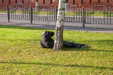 Foto de A drunkard lying on the grass wakes up on a sunny afternoon - Imagen libre de derechos