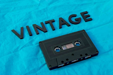 Foto de Top View of VINTAGE black lettering word with an old black cassette over a blue cloth. Fashion and music concept - Imagen libre de derechos