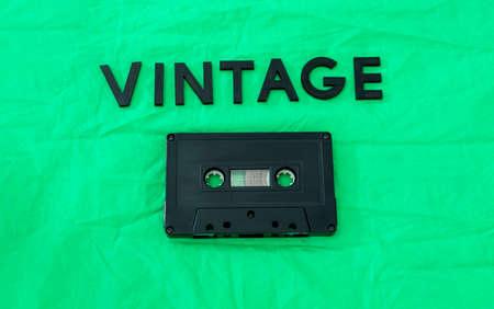 Foto de Top View of VINTAGE black lettering word with an old black cassette over a green cloth. Fashion and music concept - Imagen libre de derechos