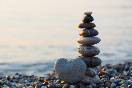 Foto de Grey stone in shape of heart in front of balanced stones on still water background - Imagen libre de derechos