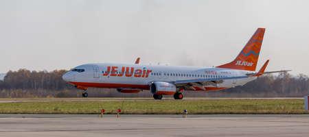 Foto de Russia, Vladivostok, 10/13/2017. Passenger jet aircraft Boeing 737-8AS of JeJu Air takes off. Aviation and transportation. - Imagen libre de derechos