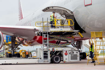 Foto de Russia, Vladivostok, 08/10/2018. Passenger airplane Boeing 777-300 of Rossiya Airlines just landed, cargo is unloaded from the aircraft. Service and maintenance of airplanes. Aviation and transportation. - Imagen libre de derechos