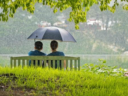A couple on a bench under umbrella