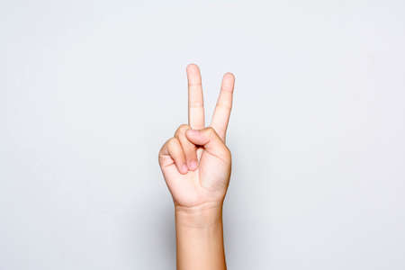 Photo pour Boy raising two fingers up on hand it is shows peace strength fight or victory symbol and letter V in sign language on white background. - image libre de droit