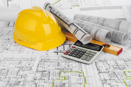 Photo for Yellow helmet, calculator, level and project drawings - Royalty Free Image