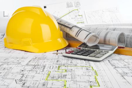 Foto de Yellow helmet, calculator, level and project drawings - Imagen libre de derechos