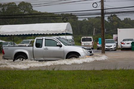 Car driving on a flooded road in rain season in island Phuket, Thailand